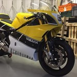 Production (Custom) Yamaha RD500/RZ500/RZV500, a black and yellow motorcycle parked on the side of a building a black and yellow Yamaha RD500/RZ500/RZV500 Sportbike parked on the side of a building