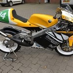 Misc. Racing Yamaha TZ250, a black and yellow motorcycle parked on the side of a road a black and yellow Yamaha TZ250 Sportbike parked on the side of a road