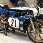 Misc. Racing Yamaha TZ250, a bicycle is parked next to a motorcycle a bicycle is parked next to a Yamaha TZ250 Sportbike