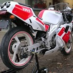 Production (Stock) Yamaha TZ250, a motorcycle parked on the side of a dirt field a Yamaha TZ250 Sportbike parked on the side of a dirt field