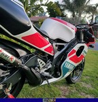 Production (Stock) Yamaha TZR250, 1992 Yamaha TZR250R SP. A red motorcycle parked in a grassy area a red and black 1992 Yamaha TZR250 Sportbike parked in a grassy field