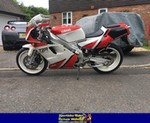 Production (Stock) Yamaha TZR250, a red Yamaha TZR250 parked on the side of a road