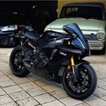 Production (Stock) Yamaha YZF-R1, a motorcycle parked on the side of a car a Yamaha YZF-R1 Sportbike parked on the side of a car