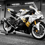 Production (Stock) Yamaha YZF-R1, a woman sitting on a motorcycle a Yamaha YZF-R1 Sportbike parked on the side of a building