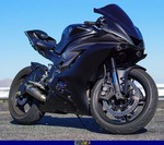 Production (Custom) Yamaha YZF-R6, a black and blue motorcycle parked on the side a black and blue Yamaha YZF-R6 Sportbike parked on the side