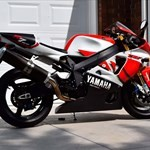 Production (Stock) Yamaha YZF-R7, a red and black motorcycle is parked on the side of a road a red and black Yamaha YZF-R7 Sportbike is parked on the side of a road