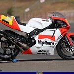 MotoGP Premier Yamaha YZR500, a red and black motorcycle is parked on the side of a road a red and black Yamaha YZR500 Sportbike is parked on the side of a road